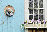 Picturesque Cape Cod barn with flowering window box and decorated straw hat on door.