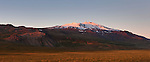 The last light of day illuminates Sn&aelig;fellsj&ouml;kull, a 1,446 meter (4,744 foot) stratovolcano located in western Iceland. The volcano, which is active, last erupted approximately 1,800 years ago, creating lava fields at its base. The mountain is technically named Sn&aelig;fell; Sn&aelig;fellsj&ouml;kull is the name of the glacier at its peak. It is commonly called Sn&aelig;fellsj&ouml;kull, however, to avoid confusing it with several other mountains with the same name. Sn&aelig;fellsj&ouml;kull means &quot;snow glacier mountain,&quot; and it was featured in the 1864 novel &quot;A Journey to the Center of the Earth&quot; by Jules Verne.