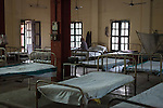 A leprosy patient sits on his hospital bed in the mens ward at the Avadhoot Bhagwan Ram Kustha Sewa Ashram
