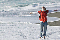 Happy female wading through water on empty beach, Hokitika, New Zealand