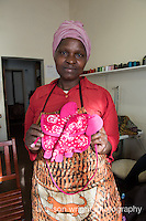 Africa, Malkerns, Swaziland, Nest organization artisans project. Nest is partnering with Baobab Batik & local artisans to help market their batik products to global markets and better sustain their local community. Khanyisile Fakudze (46) sewing at Baobab Batik. She's been a seamstress for 12 years. Has 5 children, 4 grandchildren and this helps with their school fees. With little elephant purse that she made.