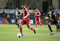 Chicago Fire defender Gonzalo Segares (13) dribbles the ball while being pursued by Philadelphia Union midfielder Keon Daniel (26).  The Chicago Fire defeated the Philadelphia Union 1-0 at Toyota Park in Bridgeview, IL on March 24, 2012.