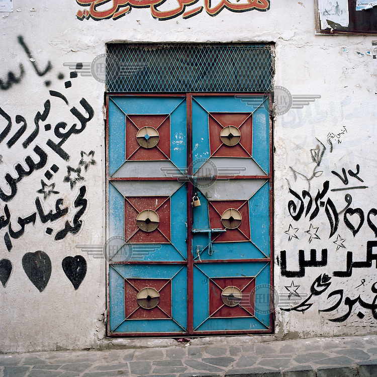 Colourful metal door surrounded by graffiti..
