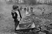 Moving some old bricks in the wheelbarrow to a pile behind the main building, Summerhill school, Leiston, Suffolk, UK. 1968.