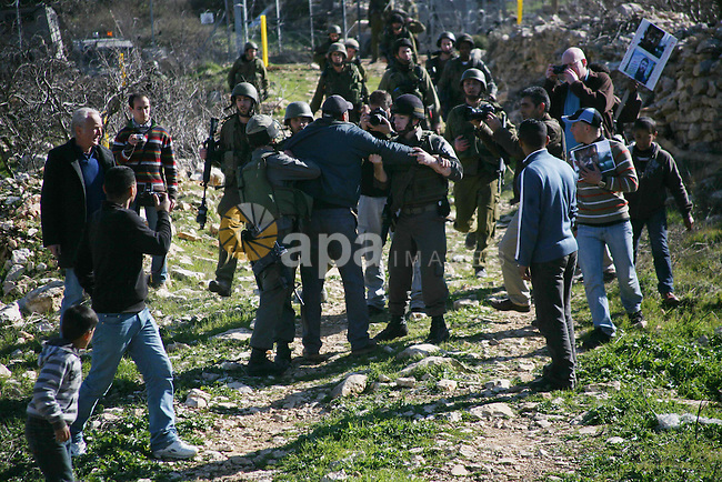 Israeli soldiers arrest a demonstrator during scuffles with Palestinians in a weekly protest against Israel's controversial separation barrier in the West Bank village of Beit Omar, close to city of Hebron and the settlement of Karmei Tzur, 11 February 2012.  Photo by Mamoun Wazwaz