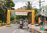 The town's welcome sign is decorated with colorful greetings banners, welcoming visitors to Sampaloc's Bulihan Fiesta in April 2012.  Meanwhile, workers decorate lampposts along the road with buri &quot;hats&quot; for the festival.