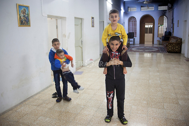 15/11/14. Alqosh, Iraq. Wassan (right bottom) and Milad (left) play with brothers Christian (second left) and Kevin (top) in a corridor at the Alqosh Orphanage.