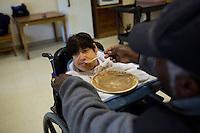 Caretakers help Fernald resident Teresa Kacinski eat lunch at the Fernald Developmental Center in Waltham, Mass., USA.