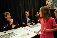 DENVER, CO--Coaches Amy Tucker and Kate Paye interact with a young fan while signing posters during a fan autograph session at the Pepsi Center for the 2012 NCAA Women's Final Four festivities in Denver, CO.