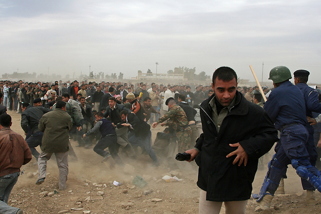 A man runs away from a melee at a police recruiting drive in Kikuk, Iraq. Police officials sought to fill 1,300 slots for the next training class, but were overwhelmed when more than 4,000 applicants showed up. More than half were turned away, and hundreds of others waited for hours, but never got a chance to submit their papers. The event was shut down after a U.S. advisor observed an Iraqi recruiting officer take a bribe from an applicant. Desperate job seekers were ordered to disperse, but many refused, so police resorted to violence to force them from the grounds. Dec. 6, 2007. DREW BROWN/STARS AND STRIPES