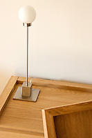 Detail of an elegant desk lamp made from stainless steel with an opaque glass globe