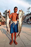Boy carrying two large fish. Puerto Vallarta, Mexico