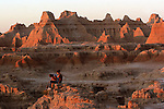 Two travelers find solace in Badlands National Park in South Dakota.  The park contains the world?s richest Oligocene epoch fossil beds, dating 37-28 million years old, the evolutionary stories of mammals such as the horse and rhinoceros arise from the 244,000 acres of sharply eroded buttes, pinnacles, and spires. Bison, bighorn sheep, endangered black-footed ferrets, and swift fox roam one of the largest, protected mixed-grass prairies in the United States.. ..