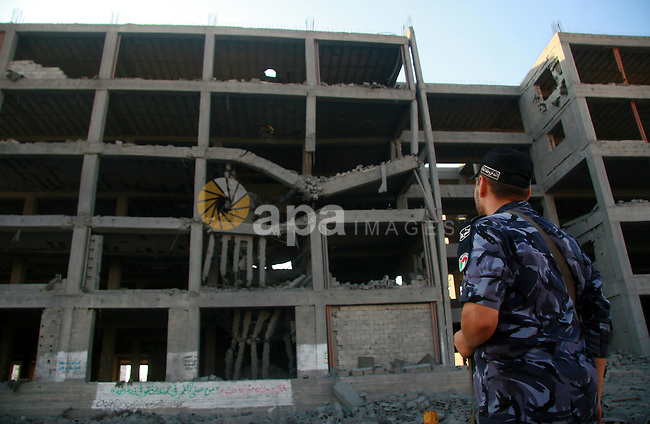 A Hamas policeman stands past a damaged government building after an Israeli air strike in Gaza August 19, 2011. Israeli aircraft struck Hamas security installations in Gaza on Friday, killing at least one Palestinian, in further retaliation for attacks along the Egyptian border in which eight Israelis died. Photo by Bashar Taleb