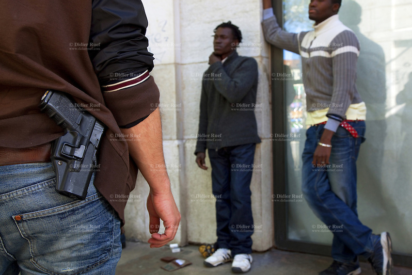 Switzerland. Geneva. A plain-clothes police officer on duty and two convict men. The black men are arrested while selling drugs in the streets. The inmate are african man from Guinea. The policeman carries a holster with a Glock hand gun. The weapon is a semi-automatic pistol designed and produced by Glock Ges.m.b.H. Glock was the first manufacturer to introduce ferritic nitrocarburizing into the firearms industry as an anti-corrosion surface treatment for metal gun parts. 3.05.12 © 2012 Didier Ruef..