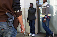 Switzerland. Geneva. A plain-clothes police officer on duty and two convict men. The black men are arrested while selling drugs in the streets. The inmate are african man from Guinea. The policeman carries a holster with a Glock hand gun. The weapon is a semi-automatic pistol designed and produced by Glock Ges.m.b.H. Glock was the first manufacturer to introduce ferritic nitrocarburizing into the firearms industry as an anti-corrosion surface treatment for metal gun parts. 3.05.12 &copy; 2012 Didier Ruef..