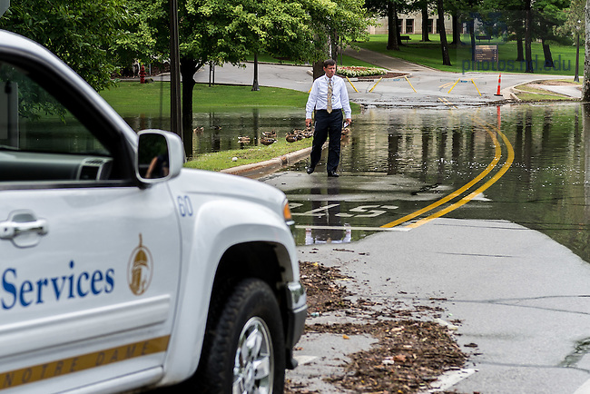 August 16, 2016; Vice President of Campus Safety Mike Seamon checks on Holy Cross Drive which was blocked near the Grotto after a record-setting rainfall. (Photo by Matt Cashore/University of Notre Dame)