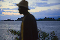 Rwanda. Western province. Kibuye. Sunset on the Kivu lake. Profile of a walking black man with a hat on the head.  © 2007 Didier Ruef