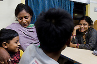 Razia Shabnam (in orange) chats with a surprised fellow passenger about her career choices and juggling motherhood while in a train with her son Saihaan (unseen), to referee an all-India invitational boxing competition in the neighbouring town of Burnpur, Calcutta, West Bengal, India. Razia Shabnam, 28, was one of the first women boxers in Kolkata. She was also the first woman in her community to go to college. She is now a coach and one of only three international female boxing referees in India. Photo by Suzanne Lee for Panos London