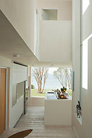 The hallway opens into the kitchen area with views of the shoreline beyond the plate glass window