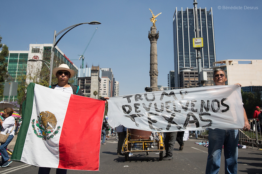 """Two Mexican men hold a sign with message: """"Trump gives Texas back to Mexico"""" during an anti-Trump march in Mexico City, Mexico on February 12, 2017. Photo by Bénédicte Desrus"""