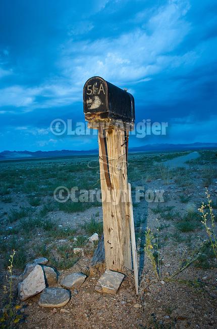 Black mailbox on post, 51A, approaching storm, near Rachel, Nev.