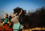 Palestinian protesters take part in clashes with Israeli troops near the border between Israel and northern Gaza strip, October 30, 2015. Since the start of October, violence that has included stabbings as well as clashes between Palestinian protesters and Israeli security forces has killed at least 65 Palestinians and 10 Israelis. Photo by Nidal Alwaheidi