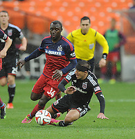 Washington D.C. - March 29, 2014:  Davy Arnaud of D.C. United gets tackled by Jhon Kennedy Hurtado of the Chicago FIre. The Chicago Fire tied D.C. United 2-2 during a Major League Soccer match for the 2014 season at RFK Stadium.