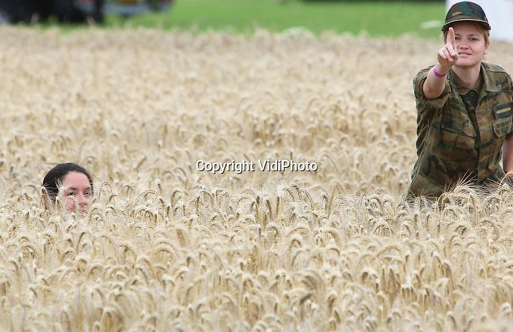 Foto: VidiPhoto<br /> <br /> VALBURG - Mocht het brood deze winter een wat andere smaak hebben, dan zou dit wel eens de oorzaak kunnen zijn. Een tweetal Zweedse vrouwelijke militairen maakt dinsdag tijdens de Vierdaagse bij het dorp Valburg van de nood een deugd en gebruikt de hoge tarwe als schuilplaats om uit de broek te gaan. En het publiek? Gewoon schijt aan hebben. Ondanks dat de wandelaars tijdens de eerste dag van de Vierdaagse van Nijmegen overal langs de route gebruik konden maken van mobiele toiletten, werden fruitbomen, struiken, sloten en akkers met mais en tarwe relatief vaak gebruikt door wildplassers. Dinsdag was de eerste dag van de 98e editie van de Nijmeegse Vierdaagse -het grootste wandelevenement ter wereld- die traditiegetrouw door de Betuwe gaat.
