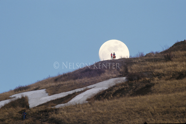 A couple and their dog on the ridge above the M are silhouetted by the full moon in Missoula, Montana