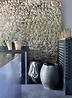 A detail of a modern kitchen with an exposed stone wall. The room is furnished with functional steel units.