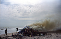 Debris and dead animal are being burnt on a beach at Nagapattinam district, Tamil Nadu.India.