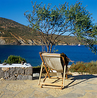 A single deck chair on a stone terrace looking out to sea