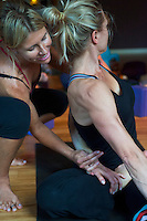 Sharon Denton assisting one of her yoga practitioners into a challenging twist pose   at the Prana Yoga Center in St. Charles, IL.