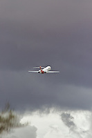 A Qantas Boeing 717 taking off into storm clouds from Alice Springs (ASP) airport