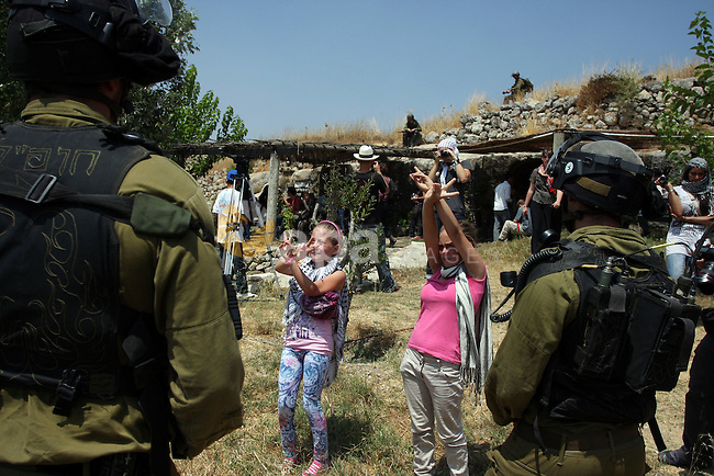 Israeli soldiers confront Palestinian children during a demonstration against Israel's separation barrier in the West Bank village of Nabi Saleh near Ramallah, Friday, June 29, 2012. Palestinians protest weekly against the neighbouring Jewish settlement of Halamish. Photo by Issam Rimawi