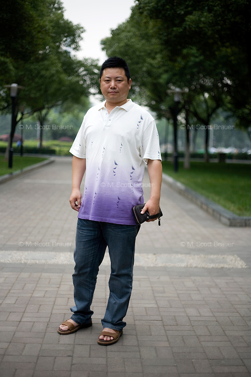 Liujun, an engineer, age 44, poses for a portrait in Nanjing. Response to 'What does China mean to you?': 'A big country.'  Response to 'What is your role in China's future?': 'Peace (written in English) Ambassador of Peace (written in Chinese)'