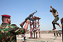 A 17th Iraqi Division trainer (l) fires blanks as a soldier jumps from atop a barrier on the obstacle during a training exercise August 30, 2010 at the Joint Security Station (JSS) Deason in Mahmoudiyah, Iraq.