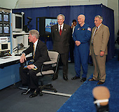 At Houston's Johnson Space Center, United States President Bill Clinton looks at a monitor while communicating long distance with the STS-90 crew preparing for a launch in two days at the Kennedy Space Center in Florida on April 14, 1998. Others pictured, in near background, are (from the left) NASA Administrator Daniel Goldin, U.S. Senator John H. Glenn Jr. (Democrat of Ohio) and JSC Director George W.S. Abbey. Clinton addressed the importance of the the Neurolab mission and asked the crew commander--astronaut Richard A. Searfoss--to profile the mission's objectives for the press corps accompanying the president on his JSC visit. Glenn is at JSC in preparation to fly as a payload specialist on the STS-95 mission later this year..Credit: NASA via CNP