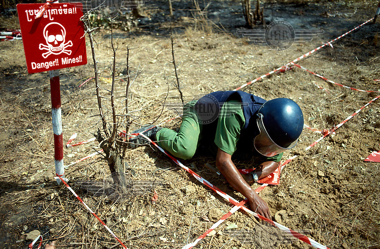 Local de-miner clearing earth from around an anti-personnel landmine in a mine field that was planted in a village by the Khmer Rouge, effectively making it uninhabitable.