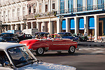 Havana, Cuba; a classic red 1950 Chevy convertible car, serving as a taxi, driving through the streets of Old Havana