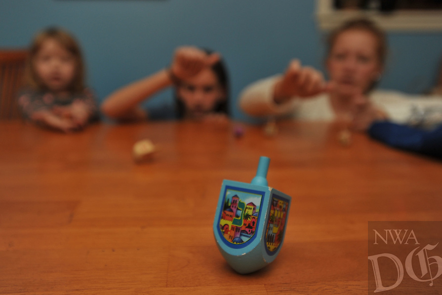 "Photo Illustration  NWA Democrat-Gazette/MICHAEL WOODS • Jewish children traditionally play with dreidels during Hanukkah. Each dreidel is inscribed with Hebrew letters that stand for Nes, Gadol, Hayah and Sham, meaning ""a great miracle happened there."" In Jerusalem, the letters are changed to reflect a different meaning: ""a great miracle happened here."""