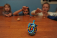 """Photo Illustration  NWA Democrat-Gazette/MICHAEL WOODS • Jewish children traditionally play with dreidels during Hanukkah. Each dreidel is inscribed with Hebrew letters that stand for Nes, Gadol, Hayah and Sham, meaning """"a great miracle happened there."""" In Jerusalem, the letters are changed to reflect a different meaning: """"a great miracle happened here."""""""