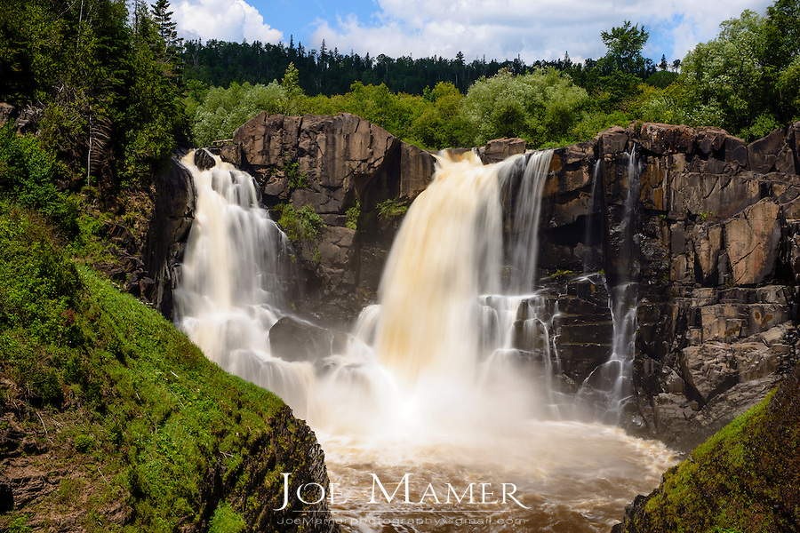 High Falls of the Pigeon River at Grand Portage State Park in summer. The Pigeon River forms part of the Canada-United States border between the state of Minnesota and the province of Ontario, west of Lake Superior. In pre-industrial times the river was a waterway of great importance for transportation and trade.