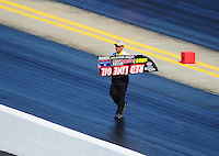 Apr. 14, 2012; Concord, NC, USA: NHRA safety safari member picks up the spill plate after it fell off the car of funny car driver Jeff Arend during qualifying for the Four Wide Nationals at zMax Dragway. Mandatory Credit: Mark J. Rebilas-
