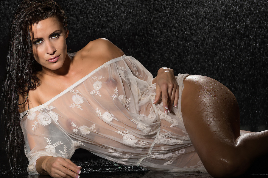 Sensual woman laying down and looking at camera with translucent dress