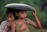 Girls Huddle under a rice basket to escape the rain. Java, Indonesia, 1983. <br />