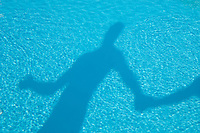Shadow in a swimming pool of a man holding the hand of another person