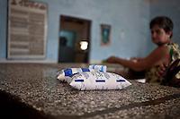 L'Avana, in un negozio quasi vuoto una signora sullo sfondo guarda due buste di latte di soja