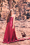 Young woman with brunette hair in red dress standing alone in the forest like a fairytale